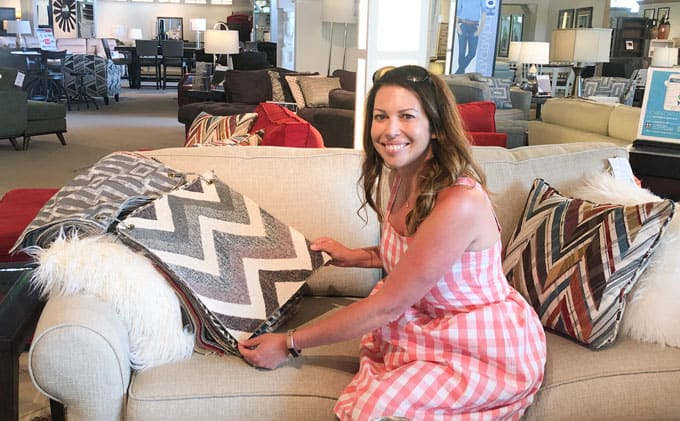 woman in pink gingham dress sitting on sofa looking at fabric swatches