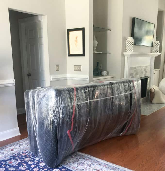 couch wrapped in fabric and plastic sitting on oriental rug