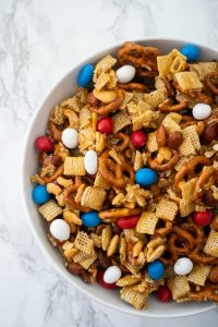 snack mix in white bowl with marble background