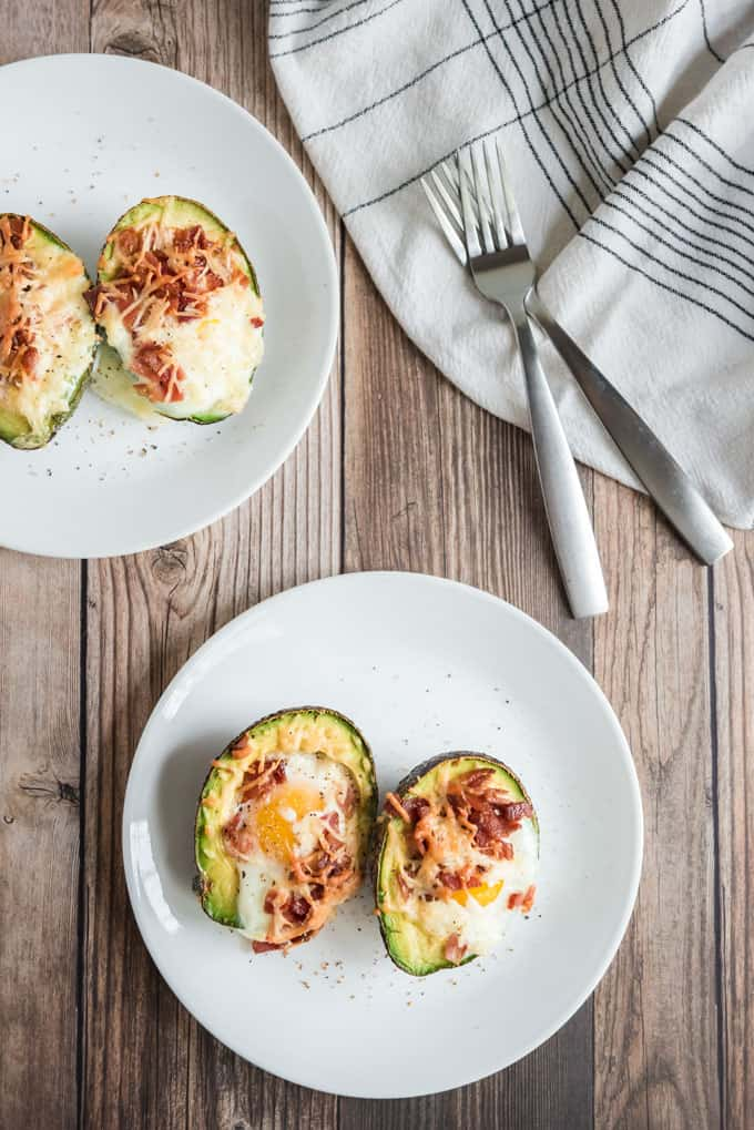 baked eggs in avocado with cheese and bacon on white plate with napkin and two forks