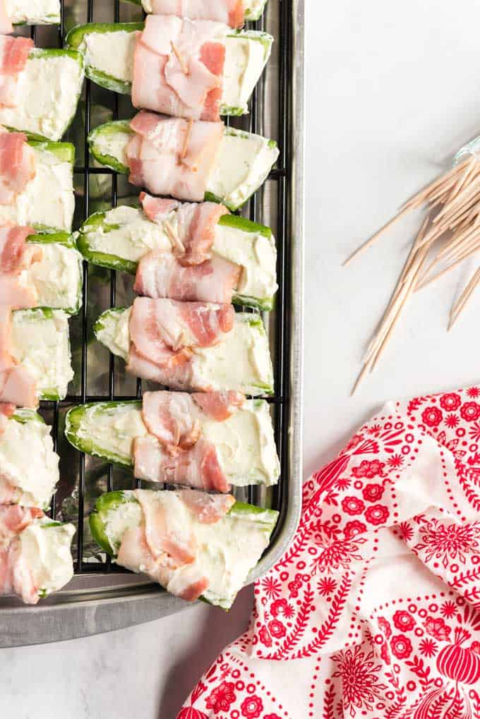 uncooked bacon wrapped jalapeño poppers on a baking sheet rack