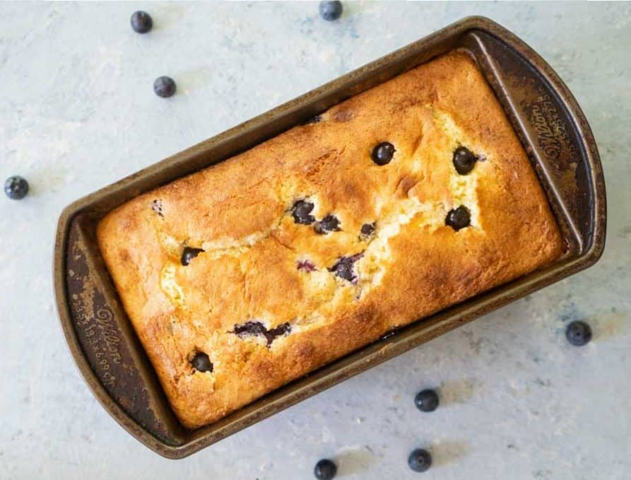 overhead view of blueberry cream cheese bread in a loaf pan with whole blueberries scatttered about