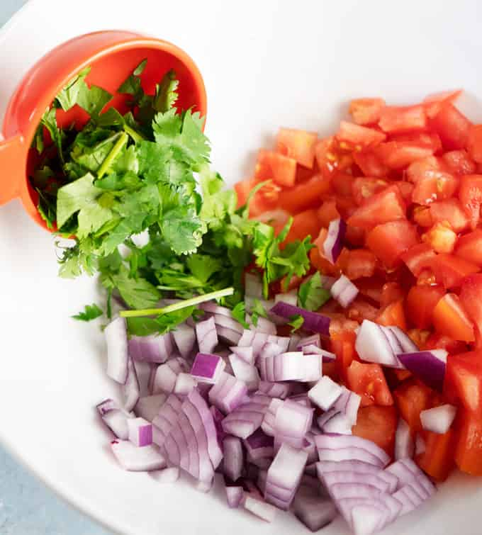 white bowl with chopped red onion, tomato and pouring cilantro our of measuring cup