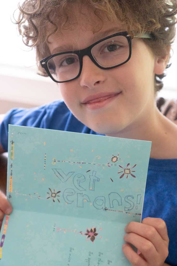 boy with curly hair holding thank you card with veterans drawn on it