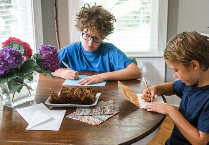 young boys sitting ar wood round table with hydrangeas and banana bread writing cards