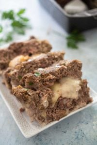 mozzarella cheese stuffed meatloaf on a white platter