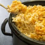 scooping crock pot mac and cheese out of slow cooker