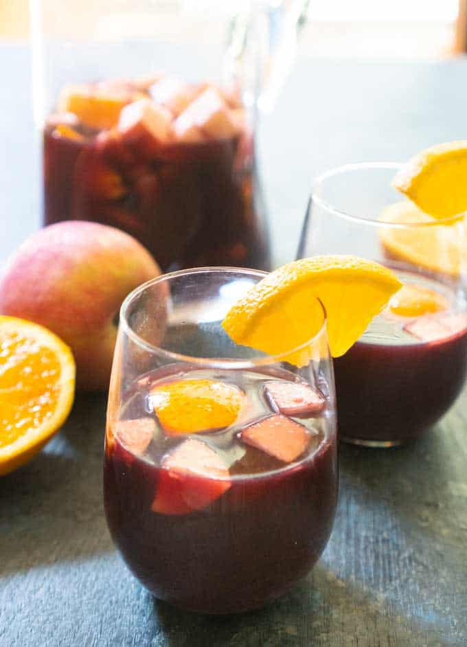red wine spanish sangria in stemless glass with chopped fruit apples oranges