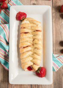 braided strawberry cream cheese danish on white plate with strawberries