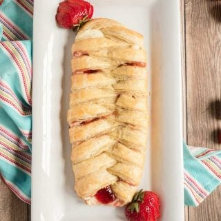 braided strawberry cream cheese danish on white plate with strawberries