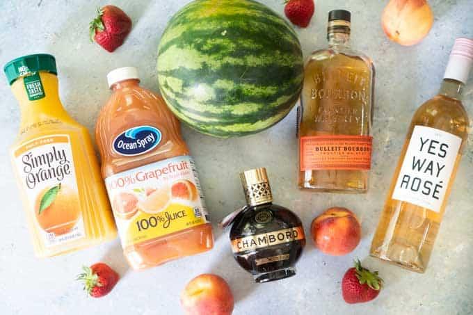 overhead view of rosé sangria ingredients: watermelon, grapefruit juice, bourbon, chambord, berries, peaches, and orange juice
