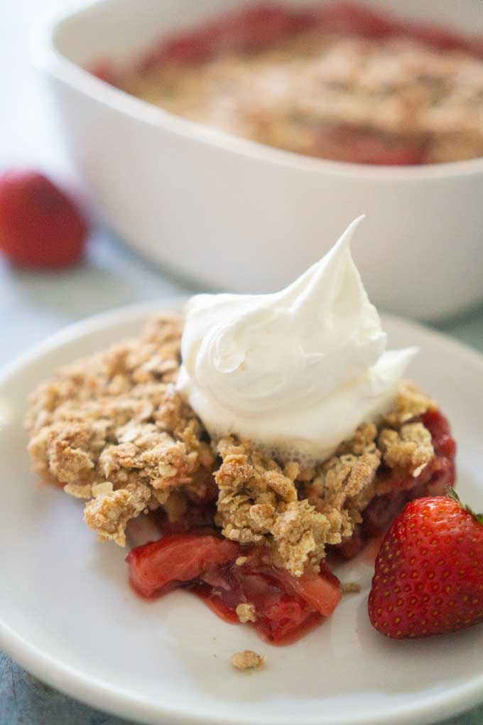 strawberry crisp with whipped cream on top on white plate with whole strawberry