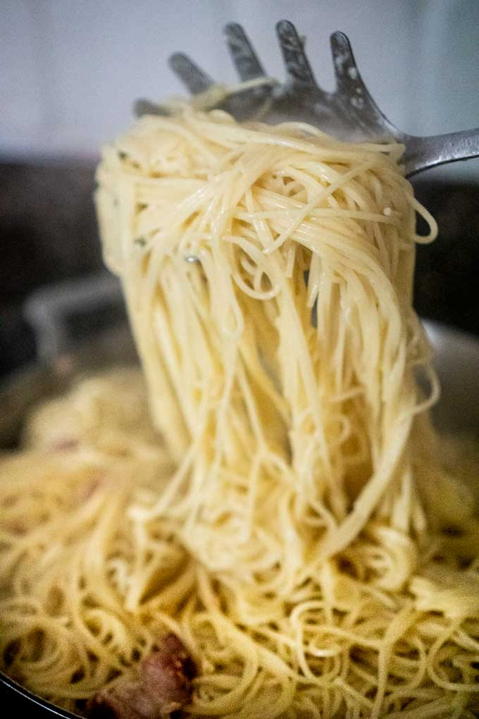 mixing egg & cheese with hot pasta to make carbonara