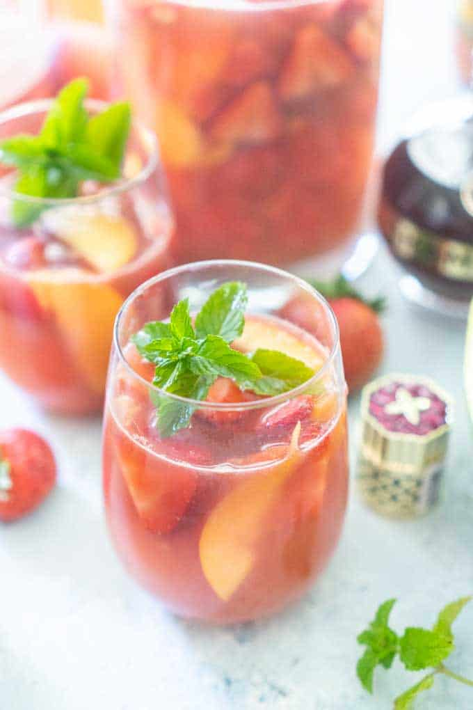 rose sangria with peaches, strawberry and watermelon with mint garnish in stemless wine glass