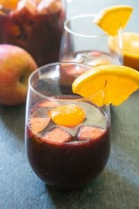 red wine sangria with cut apples and oranges in stemless wine glass