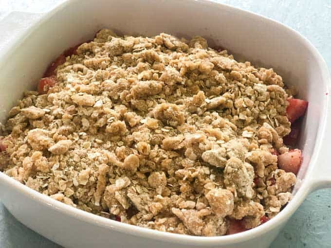 strawberry crumble before baking in white baking dish