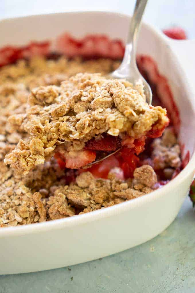 strawberry crisp with oat topping in white casserole dish