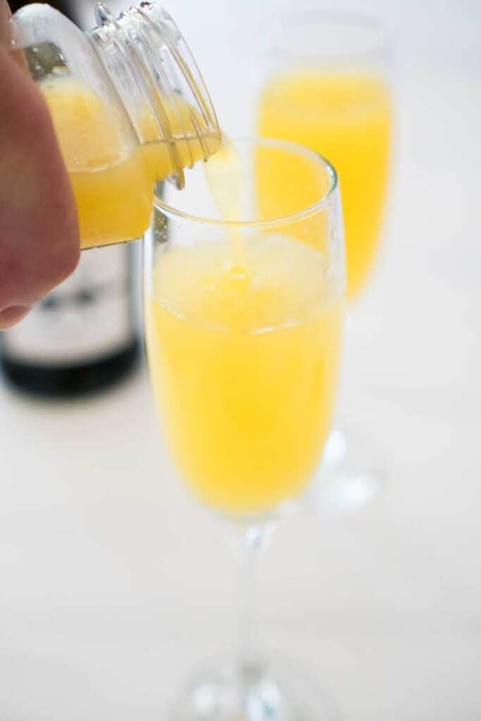 orange juice pouring into champagne flute with processo