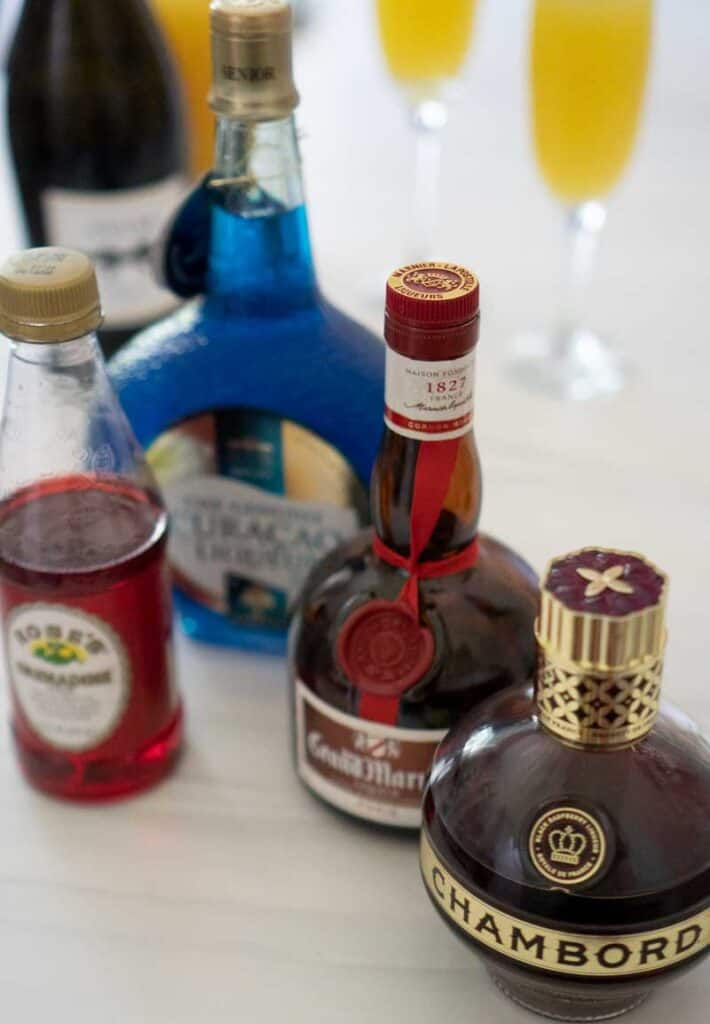 grand marnier grenadine chambord blue curacao bottles on white marble with mimosas champagne orange juice