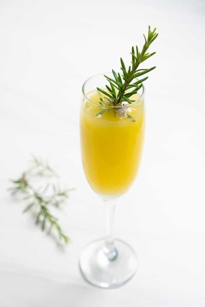mimosa in champagne flute with sprig of rosemary