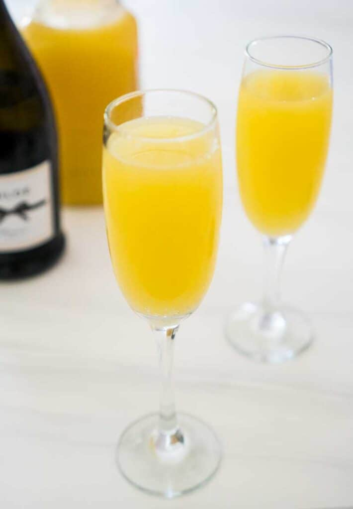 two mimosas in champagne flutes with prosecco bottle and orange juice in background on marble table