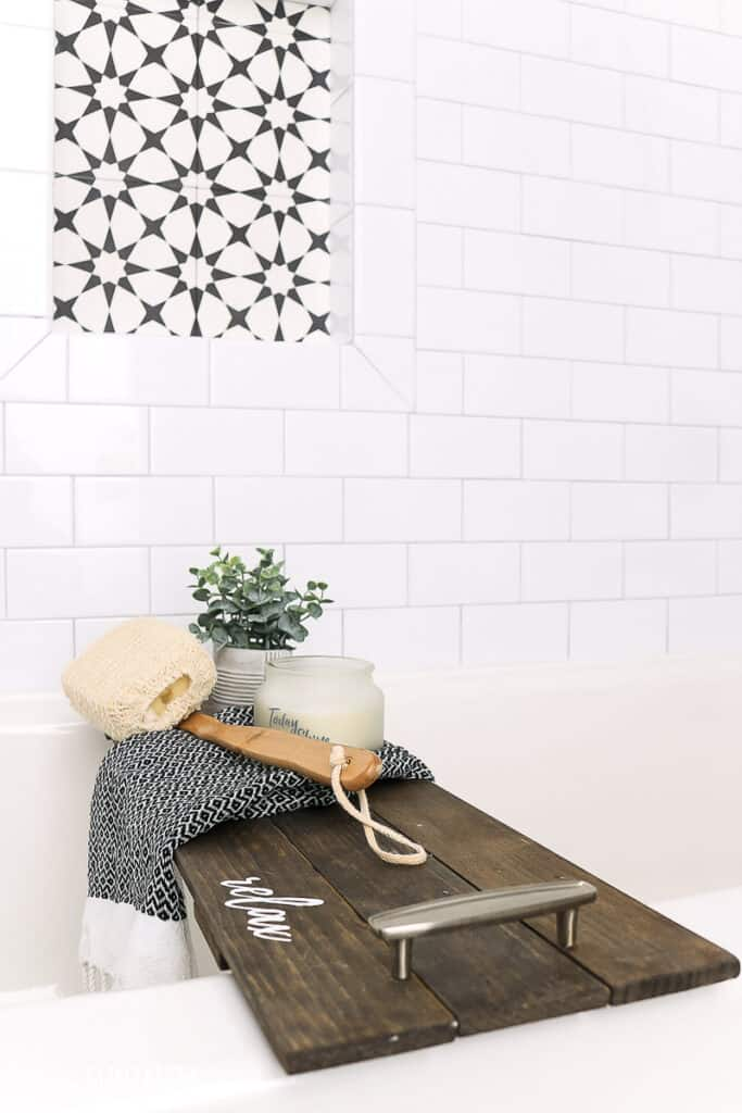 Bath tub with subway tile on the wall and a wood bath tray with loofah and small plant