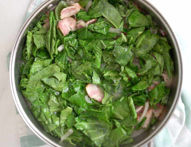 overhead view of large skillet with sliced collard greens and chopped bacon