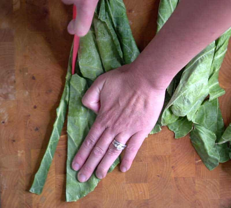 cutting collard greens stem with paring knife on wood cutting board