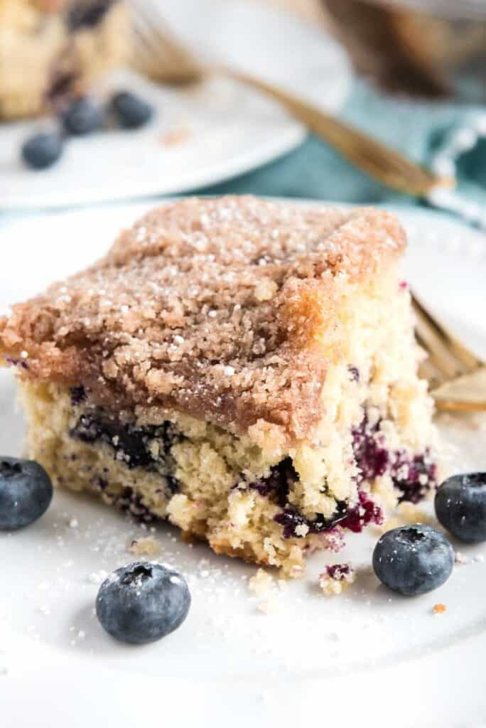 blueberry coffee cake on white plate with four blueberries