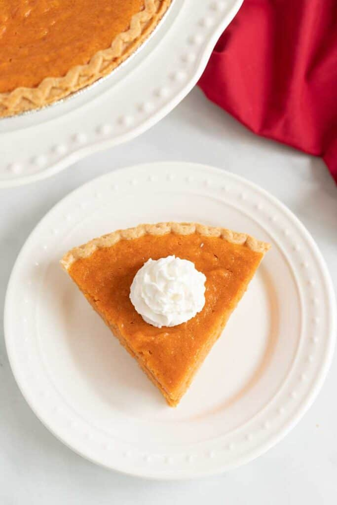 overhead view of slice of sweet potato pie with whipped cream on white plate