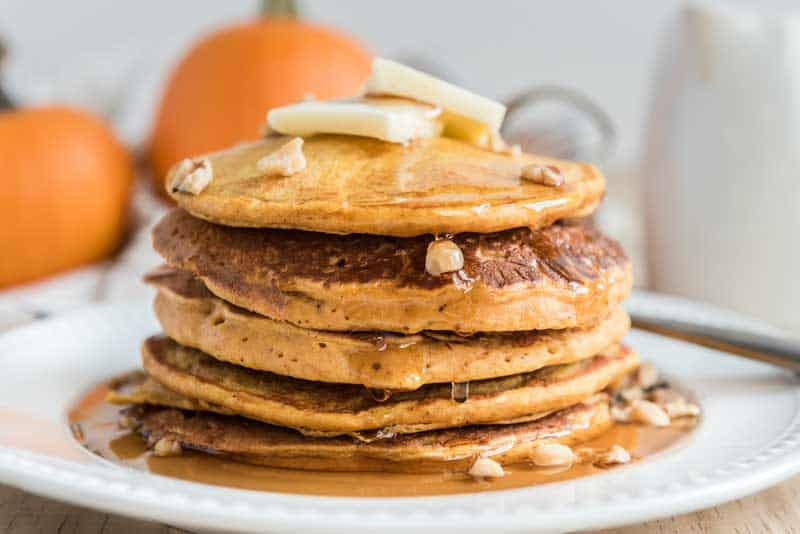 pumpkin pancakes with butter and syrup on white plate
