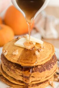 syrup pouring over stack of pumpkin pancakes