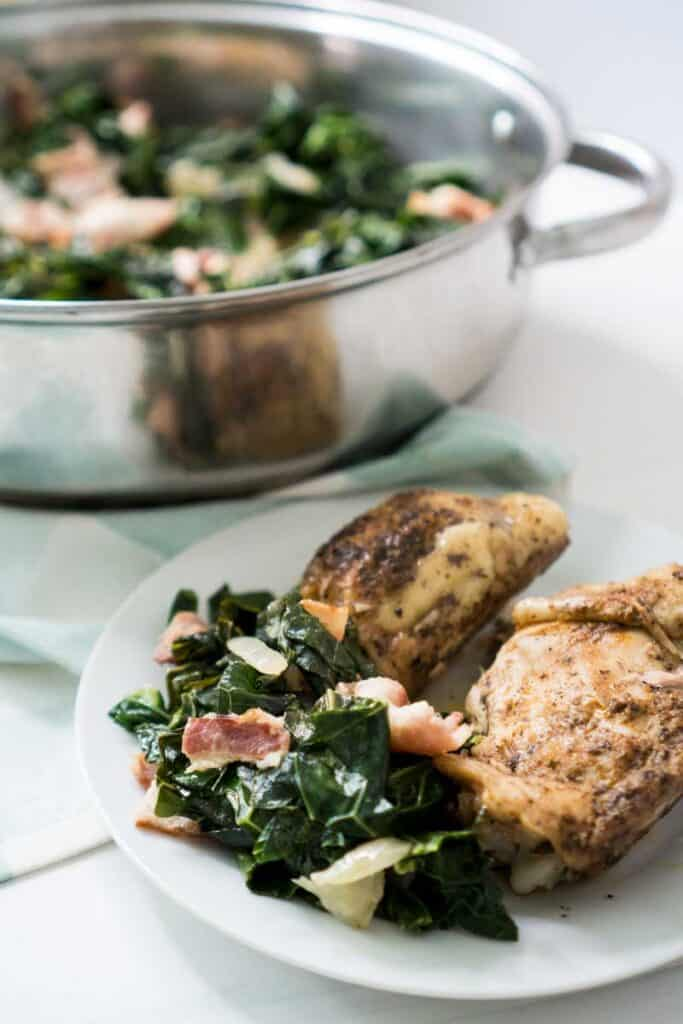 southern collard greens on white plate with chicken and large skillet filled with collards in background