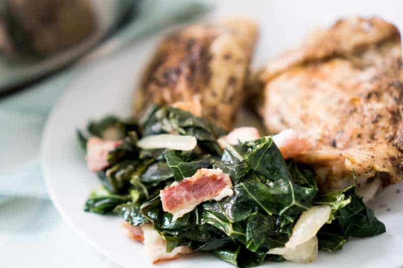 southern collard greens on white plate with chicken