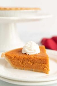 slice of sweet potato pie with whipped cream on white plate