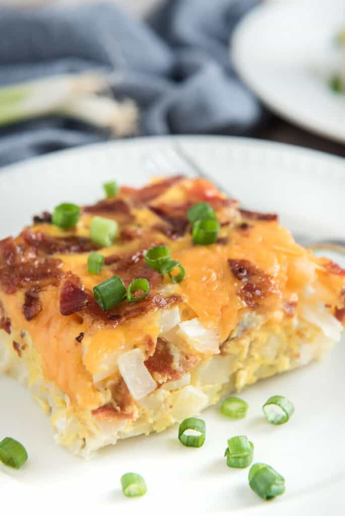 breakfast casserole witth bacon and hash browns on white plate
