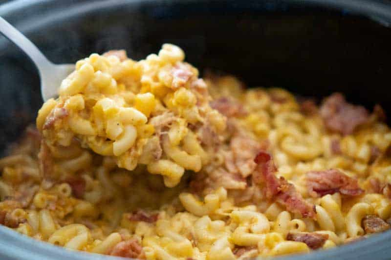 spoon scooping crock pot bacon mac and cheese