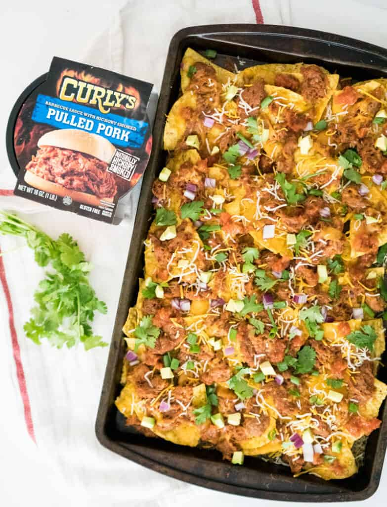 curly's bbq pulled pork container next to baking sheet of nachos with toppings