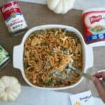 green bean casserole in white dish surrounded by canned cream of mushroom soup, green beans, crispy onions and white small pumpkins