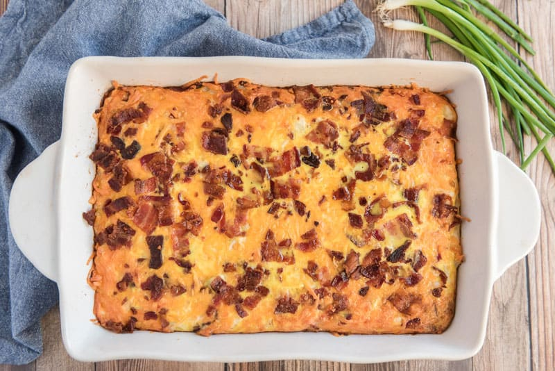 breakfast casserole with bacon and hash browns in white casserole dish