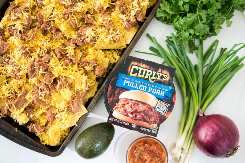 curlys pulled pork container next to baking sheet of nachos
