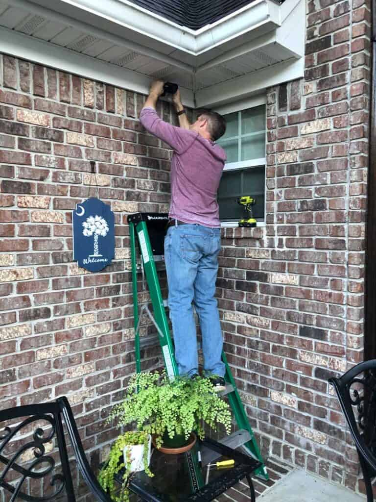 man on ladder mounting security camera to the wall