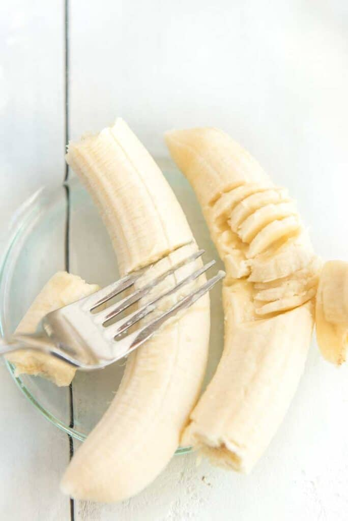 mashing bananas in glass bowl with fork