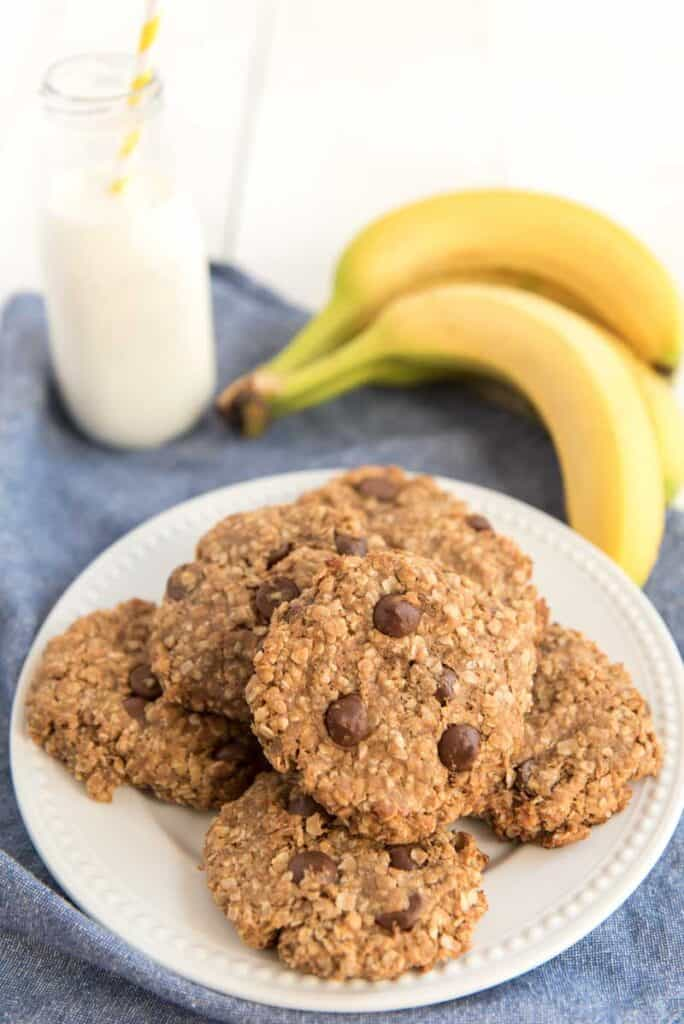 peanut butter oatmeal cookies on white plate with bananas and milk in background
