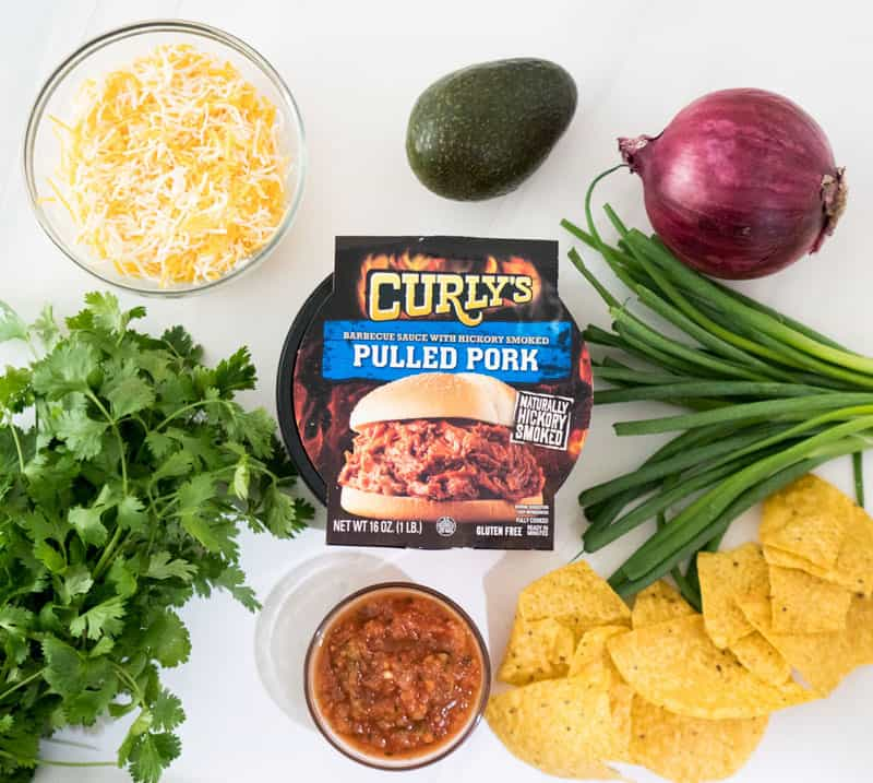 curly\'s pulled pork package on marble counter with fresh parsley and green onion red onion avocado salsa shredded cheese in a glass bowl and tortilla chips