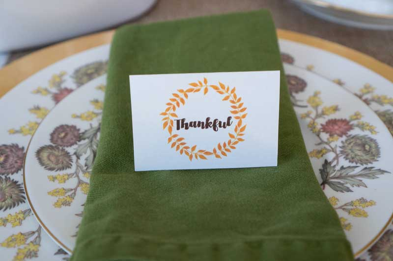 autumn themed china setting with green napkin and place card that says thankful inside an orange wreath