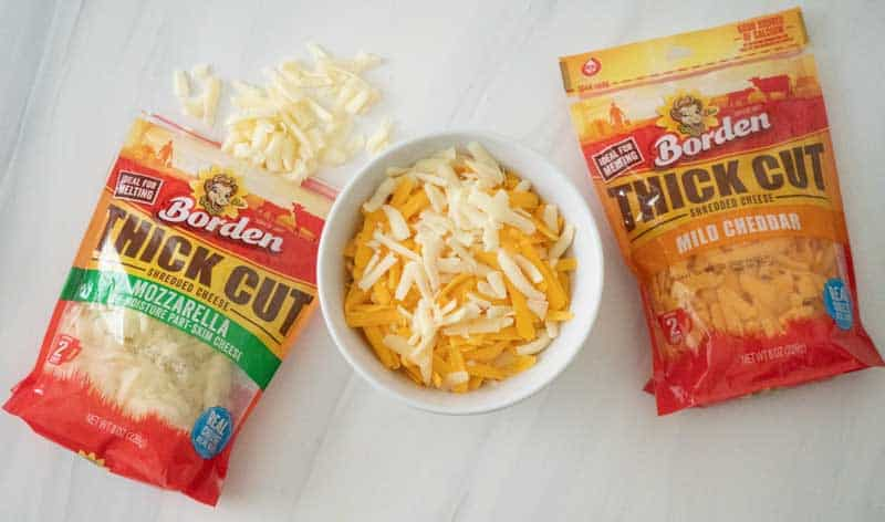 two packages of borden thick cut shredded cheese on marble counter with bowl of cheese in the middle