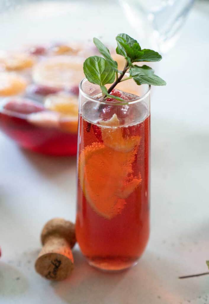 pink champagne punch in stemless flute with mint sprig garnish
