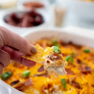 hand holding tortilla chip with chicken bacon ranch dip