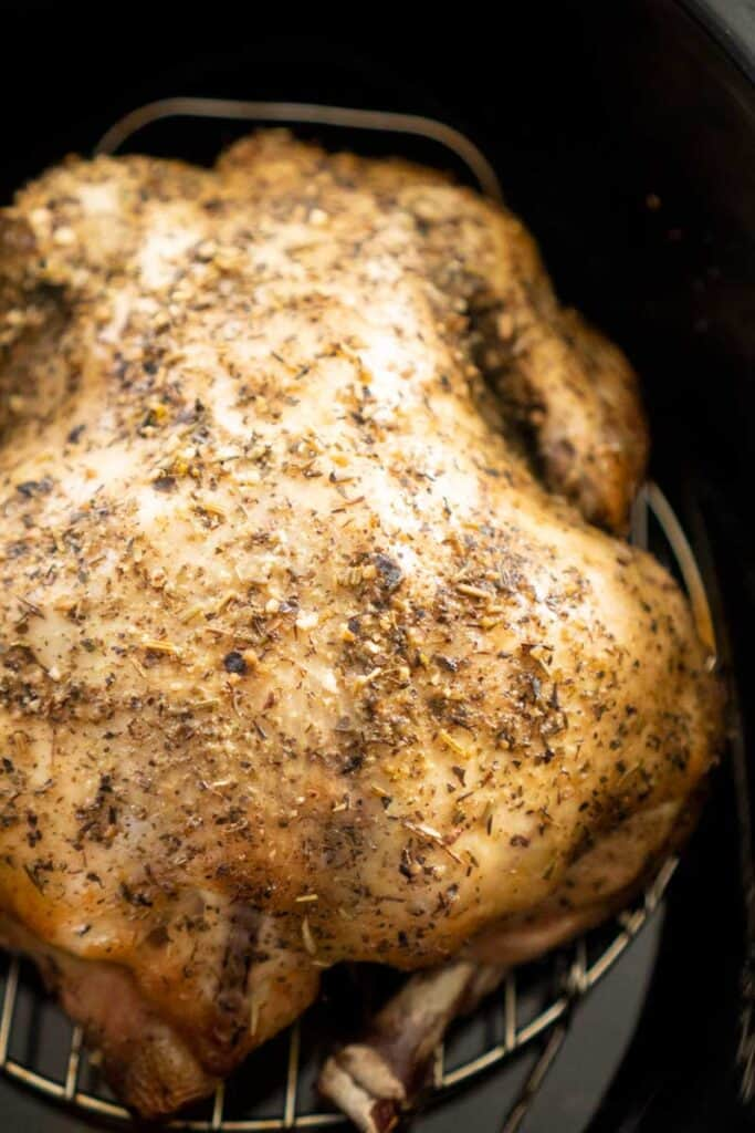 whole chicken seasoned with herbs in black slow cooker